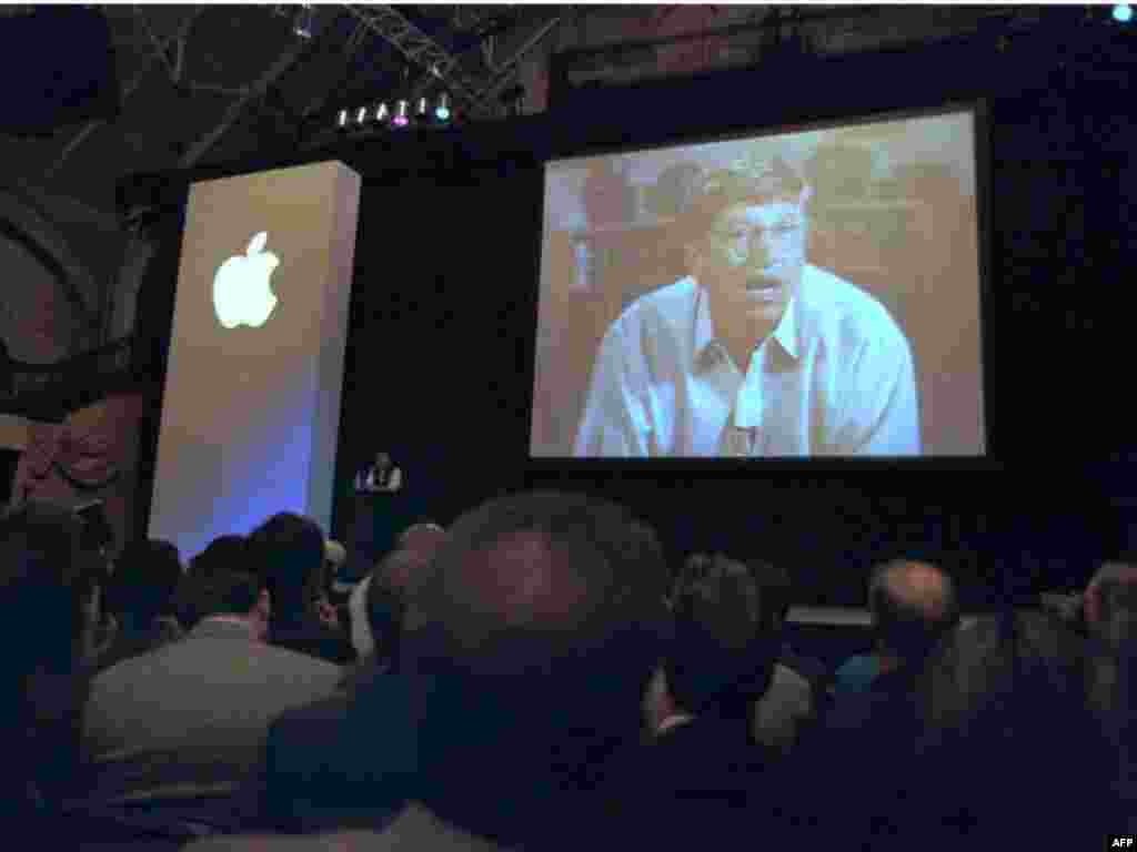 Microsoft Chairman Bill Gates appears on screen next to Apple CEO Jobs (center, on stage) to announce a partnership in August 1997 that included shareholding and Gates' seat on the Apple board.