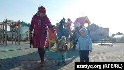 Женщина с детьми рядом с детской площадкой в микрорайоне в Шымкенте. 2 марта 2014 года.