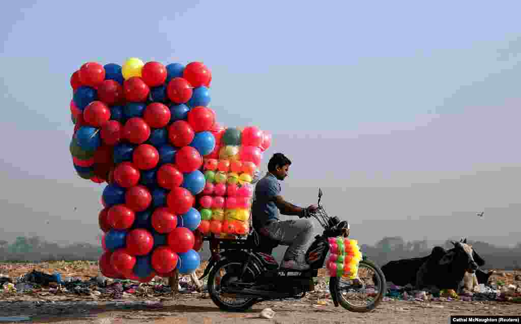 A man carries plastic balls for children on his motorcycle in Delhi. (Reuters/Cathal McNaughton)