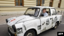 An East German Trabant decorated with reproductions of newspaper stories of the 1989 Pan-European Picnic arrives for the 20th anniversary of the gathering in Sopron.
