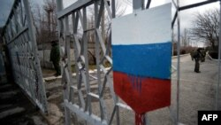 """Members of the new pro-Russian forces dubbed the """"military forces of the autonomous republic of Crimea"""" stand at a gate, adorned with a Russian flag, of Simferopol's republican military enlistment complex on March 10."""