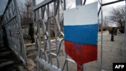 "Members of the new pro-Russian forces dubbed the ""military forces of the autonomous republic of Crimea"" stand at a gate, adorned with a Russian flag, of Simferopol's republican military enlistment complex on March 10."