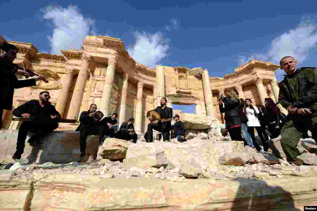 A Russian soldier stands near Syrian musicians as they play in the amphitheater of the historic city of Palmyra, Syria. Islamic State militants took control of the ancient city in May 2015 and almost immediately began destroying ancient monuments there. Syrian forces recaptured the city earlier this month. (Reuters/Omar Sanadiki)