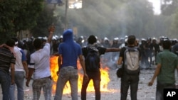 Demonstrators throw stones at Egyptian security forces close to the Interior Ministry in Cairo today.