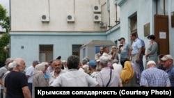 Rusiye kontrolindeki Qırım ükümetiniñ binası ögünde semetdeşlerniñ taqip etilüvine qarşı çıqqan qırımtatarlarnıñ mitingi. Aqmescit, 2020 senesi iyülniñ 8-i