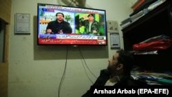A man watches a broadcast of the detailed verdict after sentencing former president Pervez Musharraf to death in a high treason case in Peshawar on December 19.