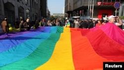 Aktivistët për të drejtat e homoseksualëve mbajnë një flamur me ngjyra të ylberit, simbol i homoseksualëve, gjatë një marshimi në Beograd më 10 tetor 2010