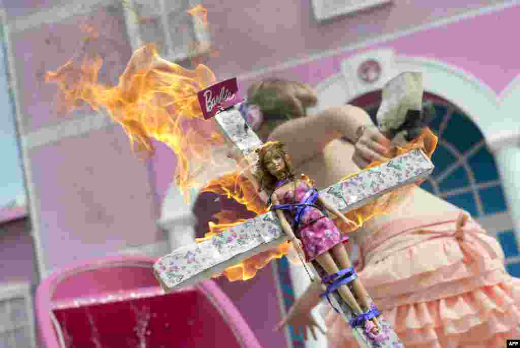 A Femen activist holds a burning crucifix with a Barbie doll affixed to it during a protest action in front of the so-called Barbie Dreamhouse in Berlin, the first life-sized mansion dedicated to the doll in Europe. Berlin feminists are mobilizing against the 2,500-square-meter mansion, which they call a sexist icon. (AFP/Barbara Sax)