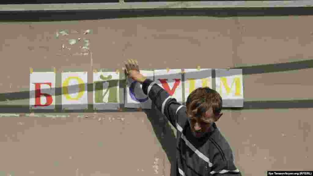 Друг Мустафаєва готує вітальний напис «бойсунмагъан» на стіні будинку, що в перекладі з кримськотатарської означає «незламний»