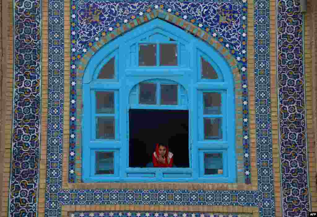 An Afghan girl looks out a window at Norouz festivities happening in the courtyard of the Hazrat-e-Ali Shrine in Mazar-e Sharif.