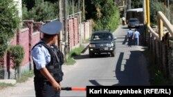 Полицейский регулирует движение на улице, недалеко от которой проходит так называемая спецоперация против подозреваемых в экстремизме. Поселок Баганашыл (в пригороде Алматы), 17 августа 2012 года.