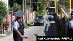 Полицейские регулируют движение недалеко от места проведения спецоперации, в ходе которой погибли 13 человек. Карасайский район Алматы, 17 августа 2012 года.