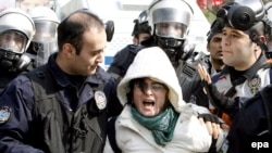 Turkish police detain a female protester outside of the Water Forum.