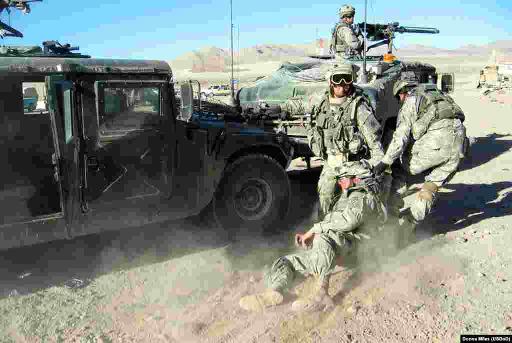 "Army medics pull a ""wounded"" comrade to a Humvee after a simulated IED attack."