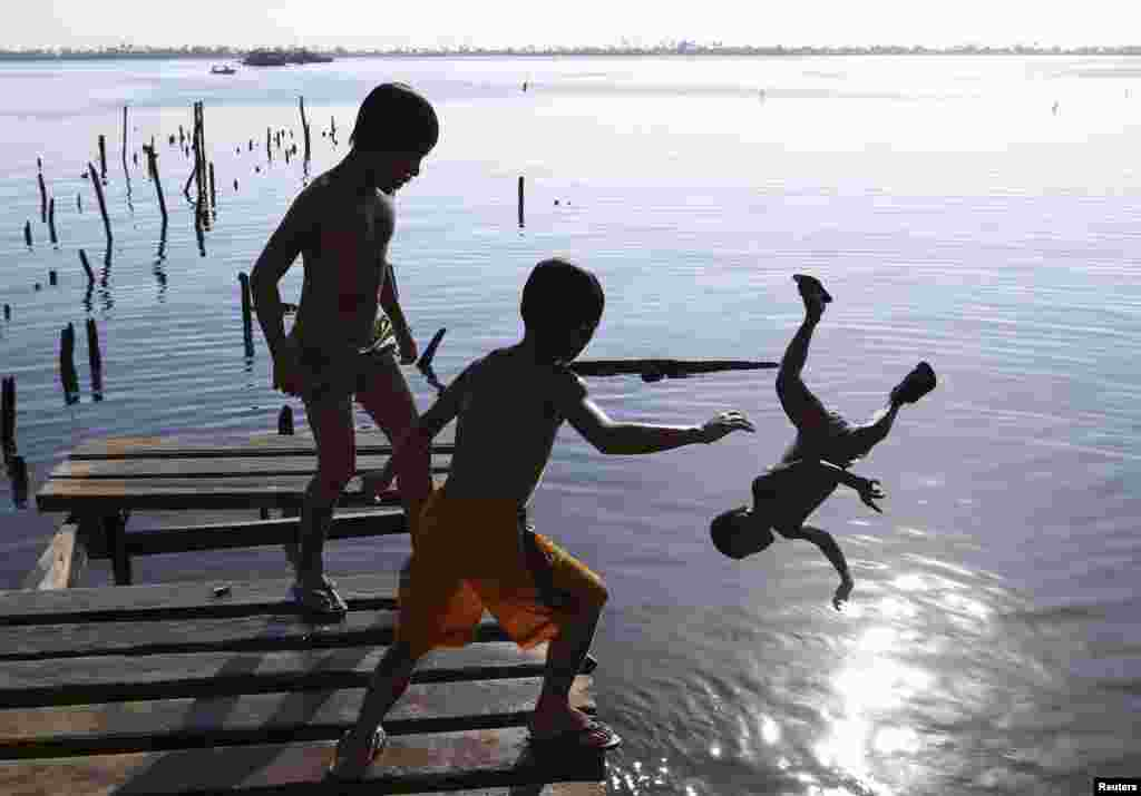 Boys jump from a foot bridge damaged by Typhoon Haiyan in the central Philippines. Almost 25,000 people still live in tents, shelters, and bunkhouses in the hardest hit regions. (Reuters/Erik De Castro)