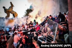 Protesters clash with police in front of Serbia's National Assembly building in Belgrade on July 8 during a demonstration against a weekend curfew announced to combat a resurgence of COVID-19 infections.