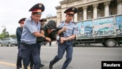 Арнайы жасақ ұсталғандардың бірін көлікке күштеп салып жатыр. Алматы, 9 маусым 2019 жыл.