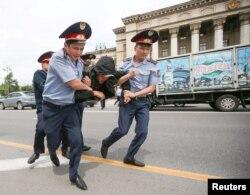Полицейлер наразылық акциясына қатысушыны көлікке күштеп салуға әкеле жатыр. Алматы, 10 маусым 2019 жыл.