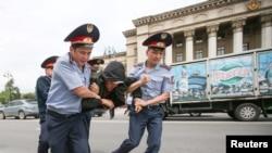 Полицейские несут задержанного на акции протеста в автозак. Алматы, 10 июня 2019 года.