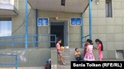 Оралман отбасылар тұратын орталықта есік алдында ойнап жүрген балалар. 2017 жыл. Көрнекі сурет.