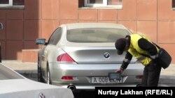 Работающий на платном паркинге мужчина фиксирует номера оставленных на стоянке машин. Алматы, 1 ноября 2017 года.