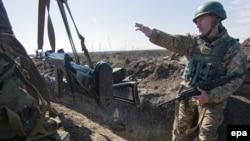 Український військовий вказує на позиції бойовиків поблизу Гнутова на Маріупольскому напрямку (архівне фото)
