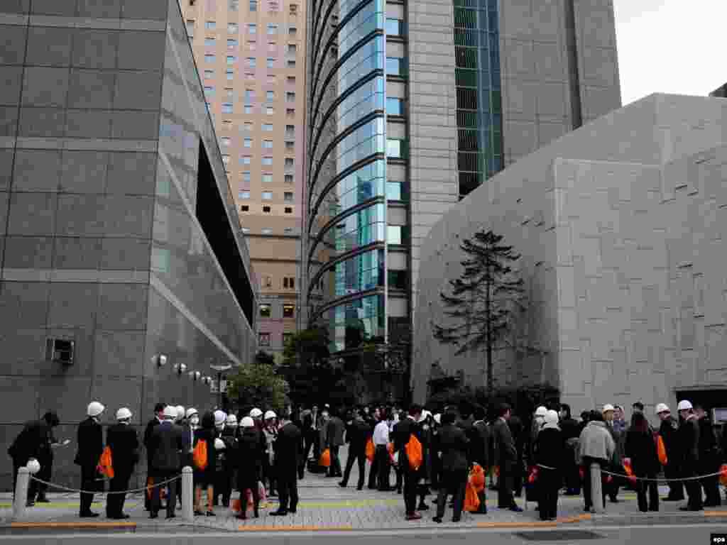 Эвакуированные из офисного центра сотрудники в Токио