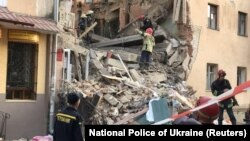 Members of Ukraine's emergency services work at the site of a gas explosion in the town of Drohobych in the Lviv region on August 28.