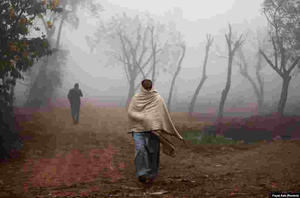 A man covers himself with a shawl as protection from cold weather as he walks amid dense fog in Peshawar, Pakistan. (Reuters/Fayaz Aziz)