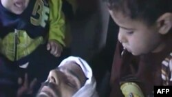 Syria -- A video grab shows two young boys sitting next to the body of a dead man identified as Yahya Hamad from Baba Amer neighborhood in Homs, undated