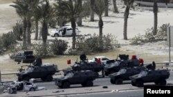 Перс булуңундагы кызматташуу кеңешине мүчө өлкөлөрдүн күчтөрү Манамадагы антиөкмөттүк демонстрациянын катышуучуларын Зумурут аянтынан көчүрүп чыгууда. Бахрейн. 16-май 2011-жыл.