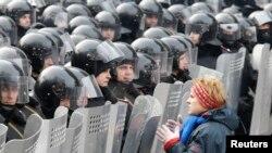 Участница протестов в Киеве стоит перед отрядом милиции. 21 января 2014 года.