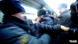 """Russian police try to separate gay-rights activists and supporters of a new law against disseminating """"homosexual propaganda"""" to minors outside the State Duma in Moscow. The bill is one considered by Human Rights Watch to be of """"an absolutely regressive and repressive nature"""" passed recently."""