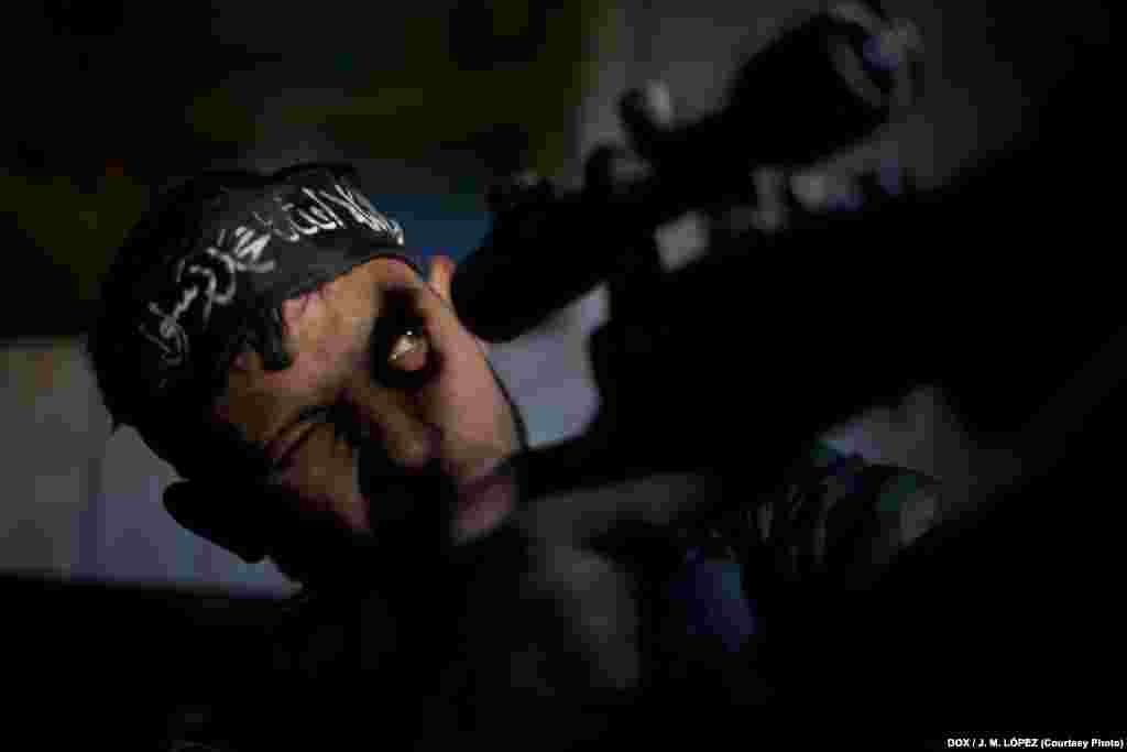 Abu Sufien, 30, aims his weapon while looking for a target inside a living room of a destroyed building in the Izaa district of the northern Syrian city of Aleppo on December 30, 2012.
