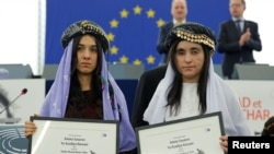 Nadia Murad Basee (left) and Lamiya Aji Bashar pose with the 2016 Sakharov Prize during an award ceremony at the European Parliament in Strasbourg, France, on December 13.