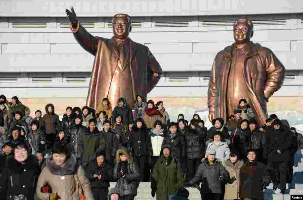 People visit in front of bronze statues of North Korea founder Kim Il Sung (left) and late leader Kim Jong Il in Pyongyang. (Reuters/Kyodo)
