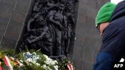 К памятнику героям восстания в гетто в Варшаве возлагают нарциссы. 19 апреля 2015 года.