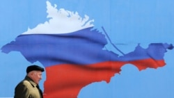 Ukraine -- A man walks past a poster depicting Crimea in the colors of the Russian flag, in Sevastopol, March 11, 2014
