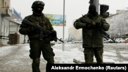 Armed, masked men block off a street in the center of the separatist-controlled city of Luhansk on November 22.