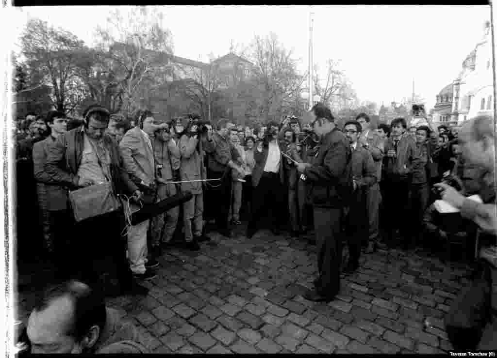"""Доц. Цветан Кардашев чете петицията на """"Екогласност"""", която организаторите възнамеряват да внесат в Народното събрание. """"Избрахме Кардашев да чете, защото имаше плътен и силен глас, а ние нямахме високоговорител"""", казва днес един от участниците в шествието Красимир Кънев. Цветан Кардашев, който вече не е между живите,тогава работи в института по философия на БАН. На заден план вдясно, с фотоапарат, повдигнат над главата, е Волен Сидеров, тогава - фоторепортер."""