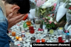 Мужчина во время поминальной акции по жертвам теракта в ноябре 2015 года в Париже.