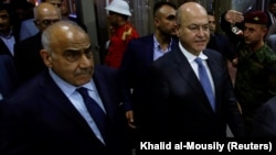 Barham Salih (right), Iraq's newly elected president, walks with new Prime Minister Adel Abdul-Mahdi at the parliament in Baghdad on October 2.