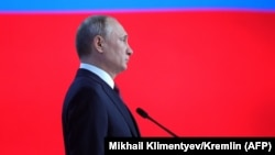 Russian President Vladimir Putin listens to the national anthem at the end of his annual state-of-the-nation address.