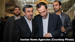 Former Iranian president Mahmoud Ahmadinejad speaking with his close aid Hamid Baghaei.