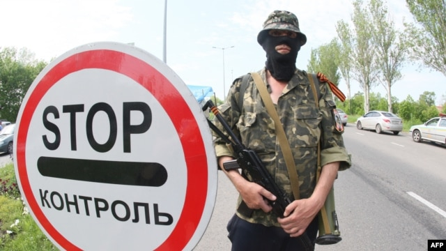 A pro-Russian militant stands guard at a checkpoint on the road from Donetsk to Mariupol.