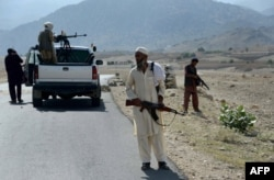 Afghan Local Police keep watch along the road near a checkpoint in Achin