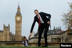 Дүйнөдөгү бою эң кыска адам Гандра Бахадур Данги эң бийик адам Султан Кузен менен рекорддордун Гинесс китебине катталган соң саламдашышууда. Лондон, 13-ноябрь 2014.