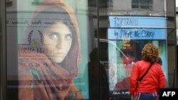 Paris. Küçədə fotoqraf Steve McCurry-nin çəkdiyi fotolara baxan qadın