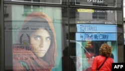 A woman in Paris looks at a poster of the famous photograph of Sharbat Gula.