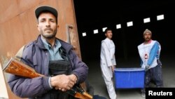 Afghan Election Commission workers carry a ballot box as a police officer stands guard at a warehouse in Herat on April 3.